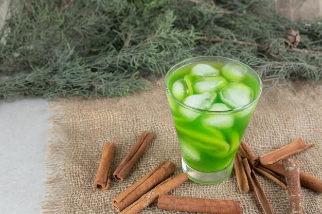Un verre de jus de kiwi et de bâtons de cannelle sur toile de jute