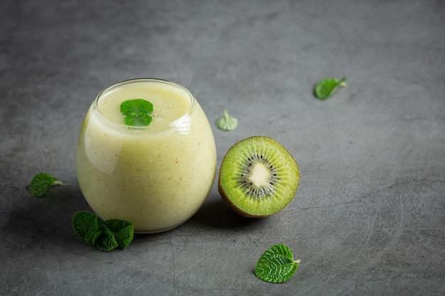 Verre de jus de kiwi posé sur un sol sombre