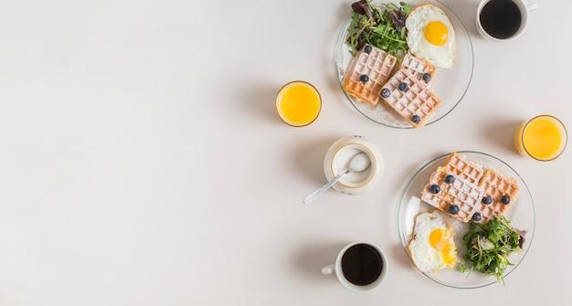 Verre de jus; lait en poudre; thé et salade saine avec gaufres et œufs au plat sur plaque sur fond blanc