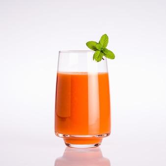 Verre de jus de légumes bio orange avec feuille de menthe sur fond blanc