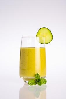 Verre de jus de légumes bio vert et jaune avec tranche de concombre et feuille de menthe sur fond blanc