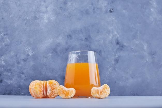 Un verre de jus de mandarine avec des fruits autour.