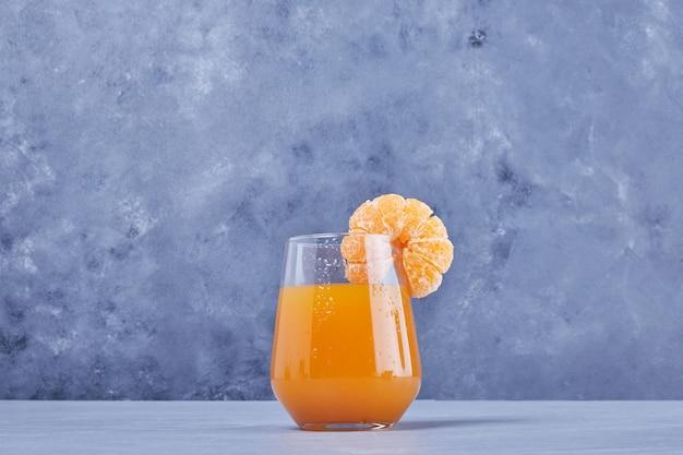 Un verre de jus de mandarine avec des fruits.