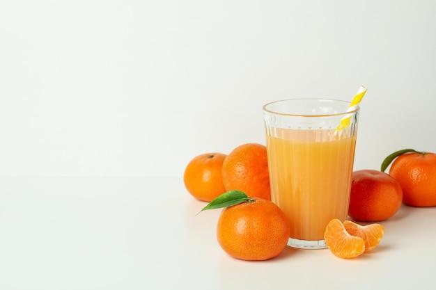 Verre de jus de mandarine et ingrédients sur fond blanc