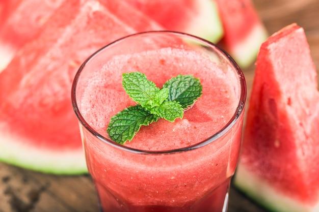 Un verre de jus de melon d'eau fraîche sur un fond de planche de bois