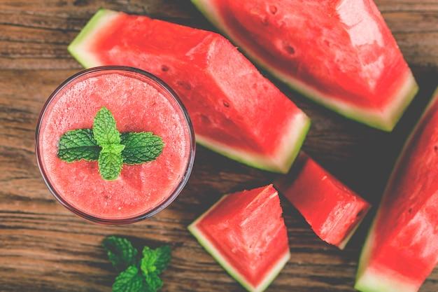 Un verre de jus de melon d'eau fraîche sur une planche de bois