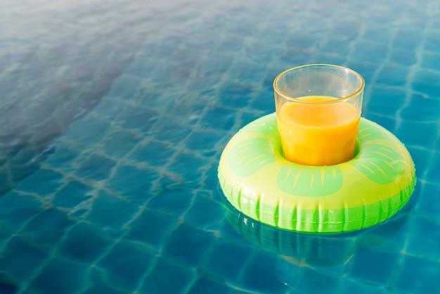 Verre de jus d'orange avec anneau de natation à la piscine extérieure