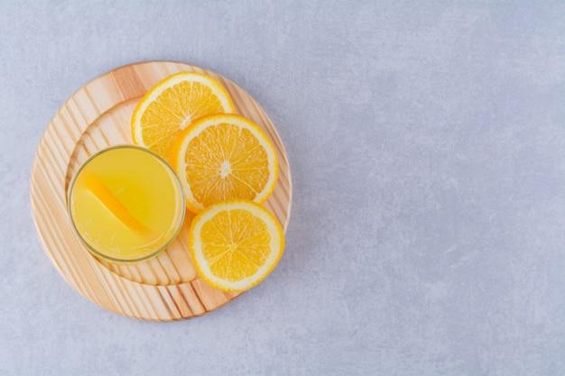 Un verre de jus d'orange à côté d'une tranche d'orange sur une plaque en bois, sur fond de marbre.