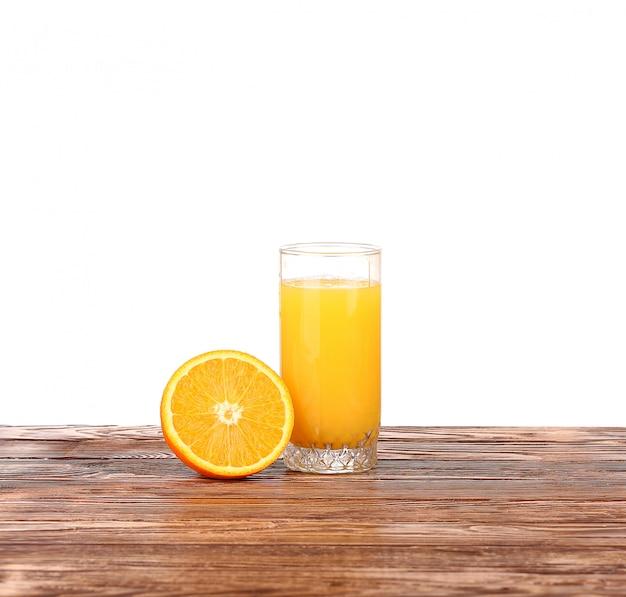 Verre de jus d'orange fraîchement pressé avec la moitié d'orange en tranches sur la table en bois