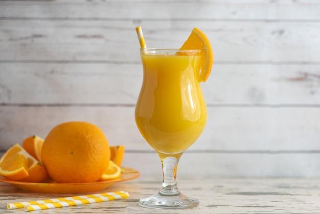 Verre de jus d'orange frais sur bois clair. vue de côté.