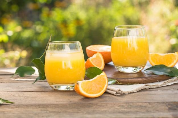 Verre de jus d'orange frais, fruits orange mûrs et tranches sur naturel. jus d'orange fraîchement pressé avec de la paille, des fruits orange et des tranches d'orange.