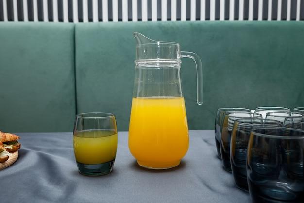 Verre de jus d'orange frais et grand pichet de boisson aux fruits.