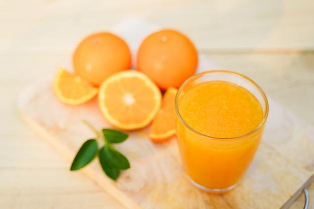 Verre de jus d'orange avec des fruits frais sur bois