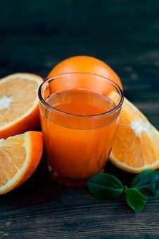 Verre de jus d'orange et un groupe d'oranges sur un tableau noir