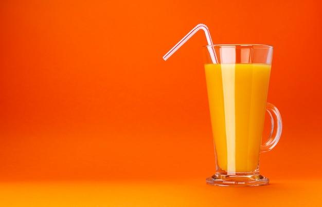 Verre de jus d'orange isolé sur fond de couleur orange avec espace copie pour le texte