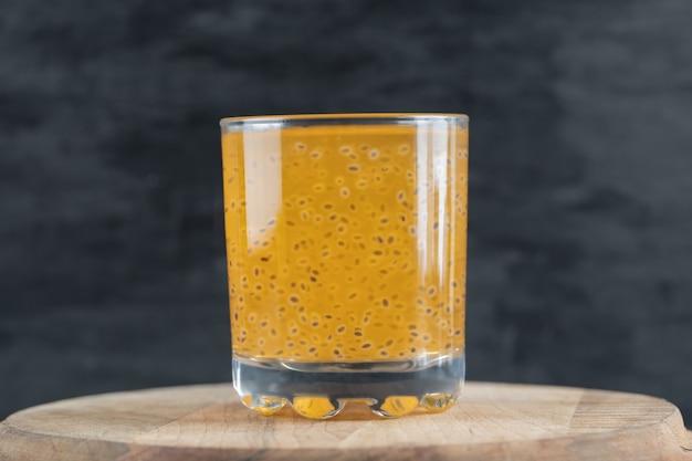 Un verre de jus d'orange jaune sur fond noir sur un morceau de planche de bois