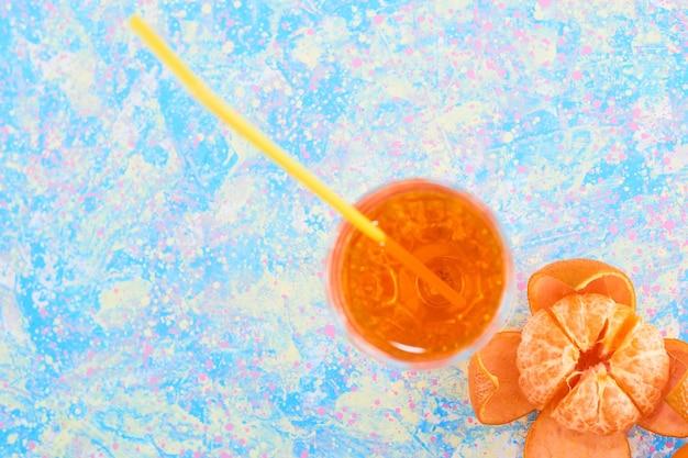 Un verre de jus d'orange avec des mandarines dans le coin inférieur. photo de haute qualité