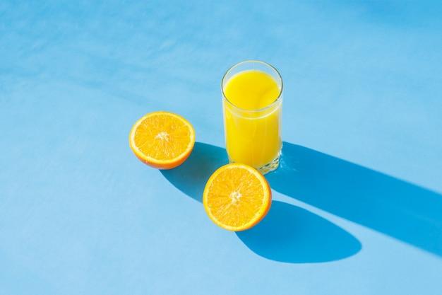 Un verre de jus d'orange et d'oranges sur fond bleu. concept de vitamines, tropique, été. lumière naturelle. mise à plat, vue de dessus.