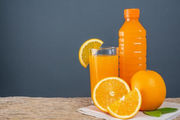 Verre de jus d'orange posé sur du bois.