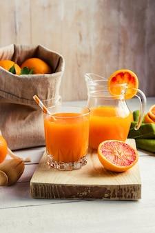 Verre de jus d'orange pressé frais et oranges sanguines sur table en bois.