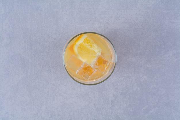 Un verre de jus d'orange sur une table en marbre.