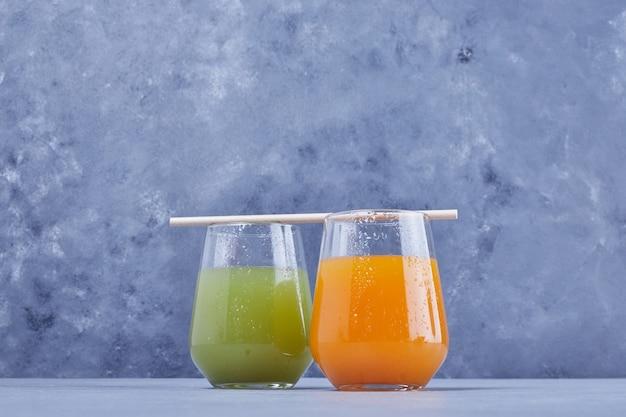 Un verre de jus d'orange avec un verre de jus de pomme.