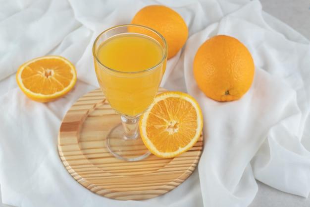Un verre de jus avec des oranges fraîches sur une plaque en bois