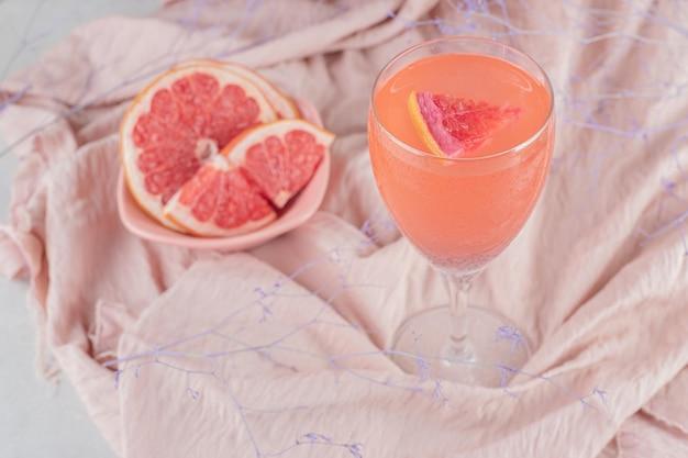 Un verre de jus et de pamplemousse frais sur tissu rose
