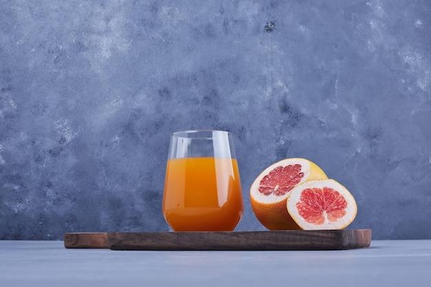Un verre de jus de pamplemousse avec une tranche de fruit autour.