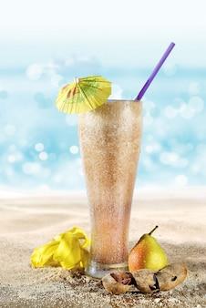 Verre avec jus de poire et tamarin sur le sable de la plage