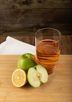 Un verre de jus de pomme au citron sur une planche de bois