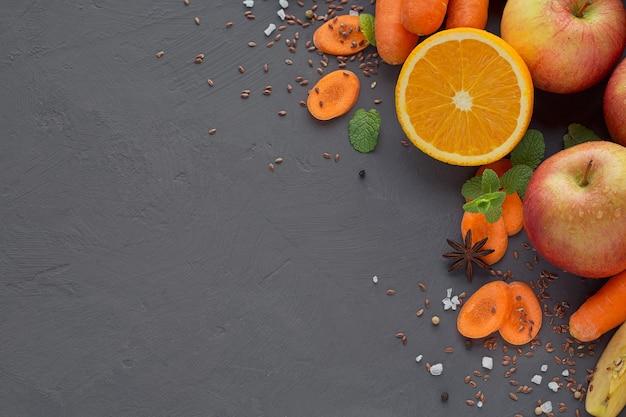 Verre de jus ou smoothie maison, fruits et légumes. carotte fraîche, pomme, citrouille, orange, pamplemousse sur table sombre. alimentation saine, alimentation, régime, désintoxication et concept végétarien.