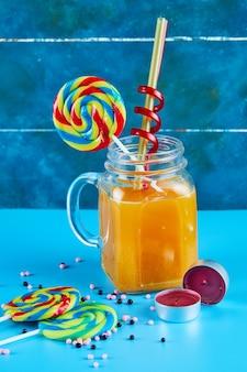 Un verre de jus avec des sucettes colorées sur une surface bleue.