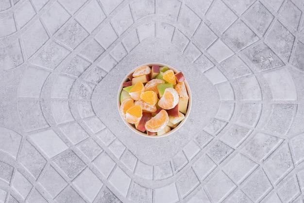 Un verre de jus avec des tranches de fruits sur fond de marbre.