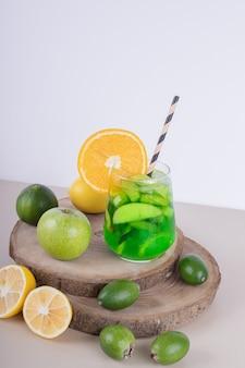 Un verre de jus avec des tranches de fruits et des fruits frais sur un mur blanc.