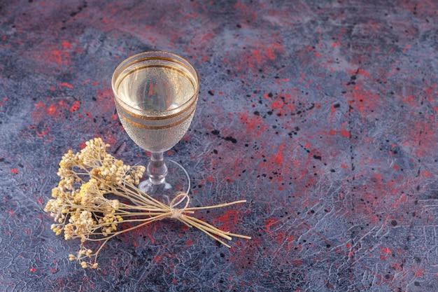 Verre de jus avec des tranches de poire et des fleurs séchées sur fond bleu.