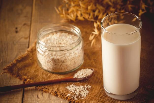 Verre de lait d'avoine sur un fond en bois sans lactose boisson d'avoine sans gluten super food