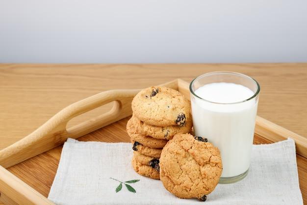 Un verre de lait et des biscuits aux raisins secs sur un plateau en bois