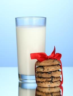 Verre de lait et biscuits sur fond bleu