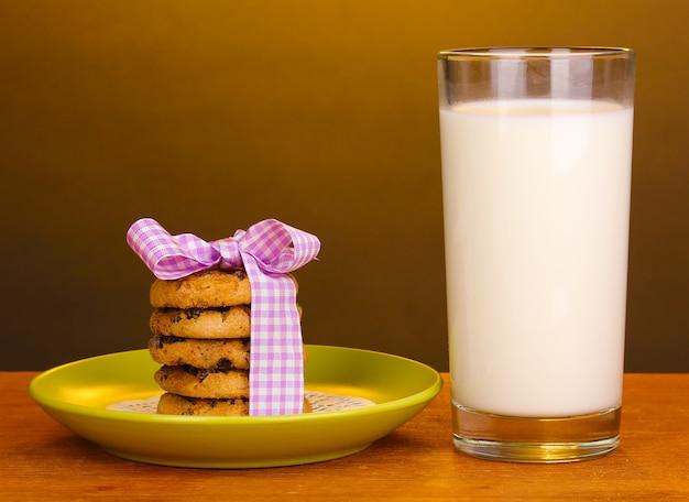 Verre de lait et biscuits sur table en bois sur fond marron