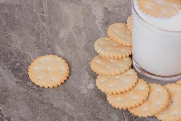 Un verre de lait avec des biscuits sur une table en marbre