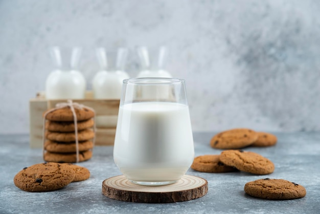 Un verre de lait chaud avec de délicieux biscuits sur une table grise.