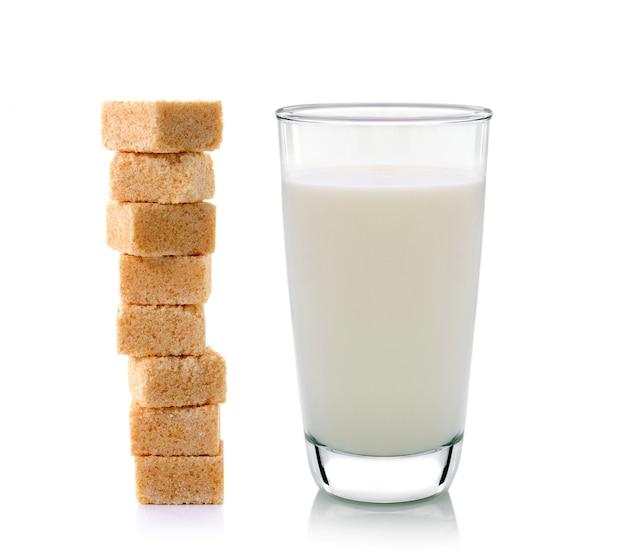 Verre de lait et de cubes de sucre de canne isolé sur fond blanc