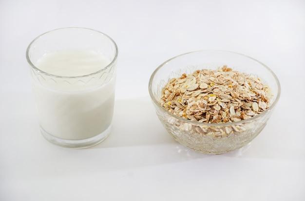 Verre de lait et de flocons d'avoine dans un bol