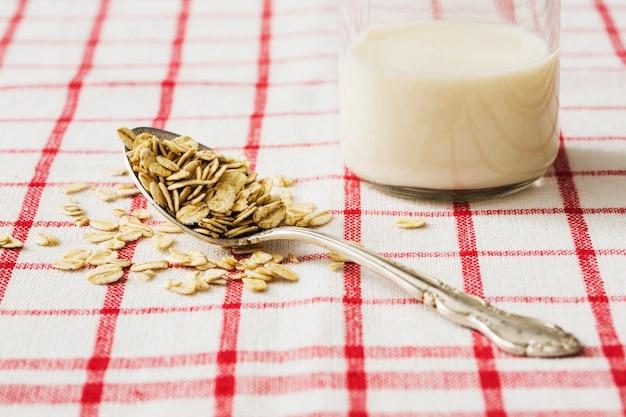 Verre de lait avec des flocons d'avoine secs sur la vieille cuillère