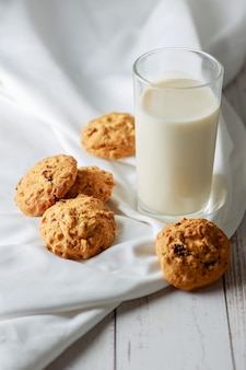 Un verre de lait frais avec des cookies aux pépites de chocolat sur fond de bois blanc alimentation saine mise au point sélective