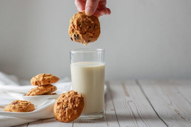 Un verre de lait frais avec des cookies aux pépites de chocolat sur une surface en bois blanc