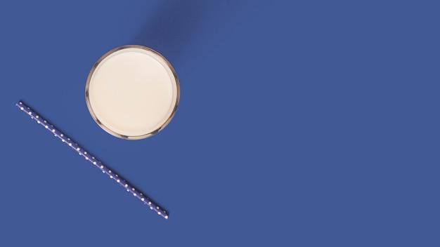 Verre de lait frais et de la paille sur le fond bleu