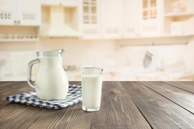 Verre de lait frais et pot sur une table en bois avec cuisine flou comme toile de fond.