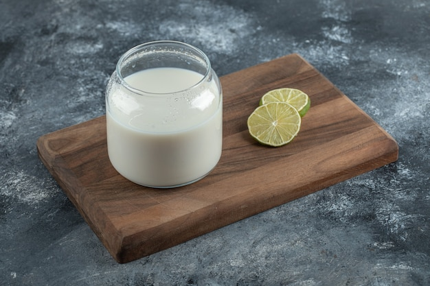 Verre de lait frais et tranches de citron sur planche de bois